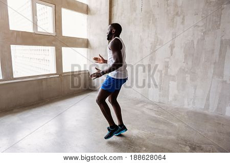 Simple movements. Bearded young sporty man is warming up. He is walking on spot and concentrating on action in empty room