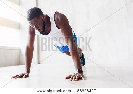 One more. Severe strong african bearded guy with strained face is training plank position. Focus on his face and arms. Copy space in right side