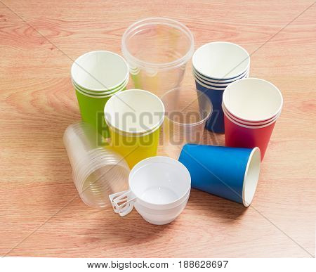 Different disposable transparent and white plastic cups disposable paper cups in red green blue and yellow colors on a wooden surface
