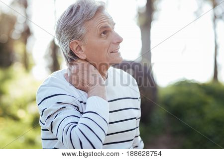 Constrained in motions. Pleasant elderly disappointed man touching his neck and feeling strong pain while sitting in the park