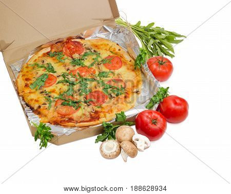 Cooked round pizza with tomatoes mushrooms and arugula wrapped in aluminum foil in the open cardboard box and fresh tomatoes mushrooms parsley and arugula beside on a light background