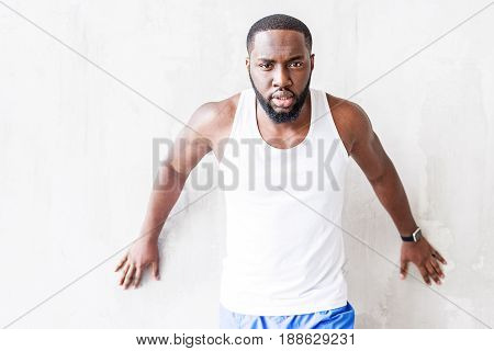 Half length portrait of young bearded athlete. Pensive muscular guy is standing by wall and touching it by his both hands. He is looking directly to camera