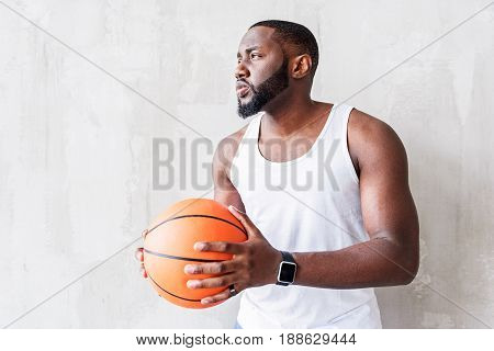 Reflective handsome african ball-gamer with beard is keeping basket-ball with two hands. He is looking away seriously