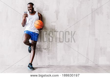 Angry muscular athlete with basket-ball is listening to music and standing close to wall. Aggression concept. Copy space in right side