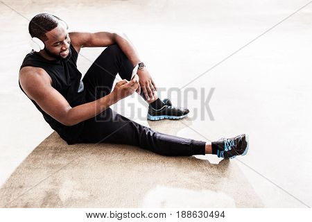 Leisure time. Joyful handsome african man is relaxing after fitness training. He is sitting on floor and listening to music on his player