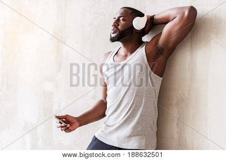 Satisfied muscular handsome man is leaning on wall and having rest with music in his headphone. Copy space in left side