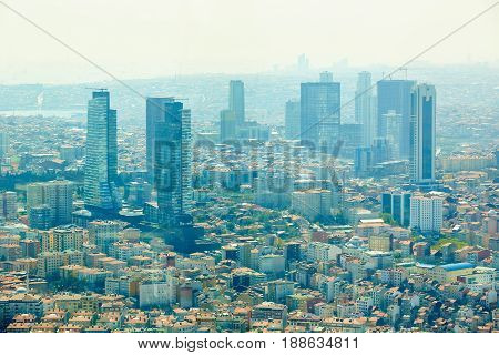 Istanbul, Turkey - 1 April, 2017: Urban landscape of European side of Istanbul and Bosphorus Strait on a horizon. Modern part of city with business towers of international corporations, skyscrapers and shopping malls of the city. Shooting through the glas