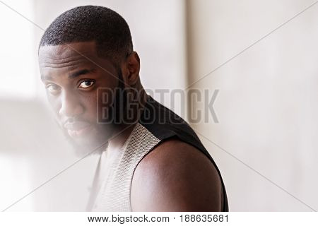 Portrait of pensive attractive man in trendy menswear looking straight at camera. Sunlight is falling down at his face. Copy space in right place