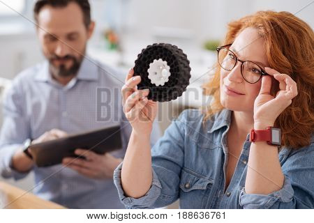 Perfect design. Smart creative beautiful woman holding a 3d model and fixing her glasses while looking at it