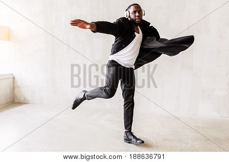 Full length portrait of pensive handsome african man in trendy long coat trying to skyrocket. He is standing on one leg with hands stretched to sides as airplane wings. Freedom concept