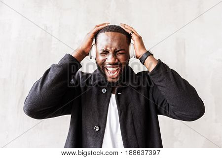 Screaming sound. Waist up portrait of overwhelm african bearded man listening to music. He is holding headphones by two hands with eyes closed and mouth opened wide