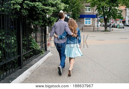Loving Couple Embracing And Walking  Through The City, Back View