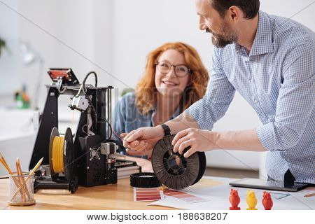 3d design studio. Professional experienced male designer holding filament and loading in into 3d printer while working with his colleague