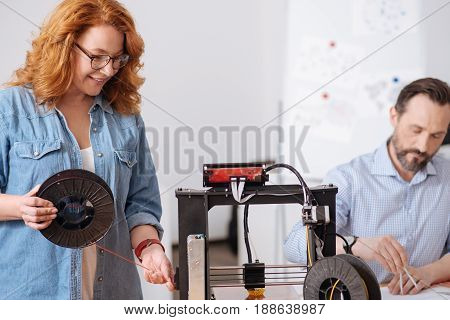 3D printer components. Nice delighted pleasant woman holding a filament coil and adjusting it to the 3d printer while standing near it