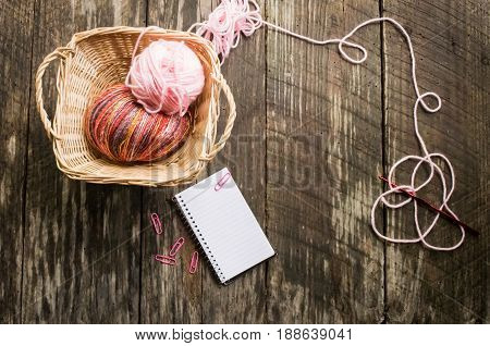 Balls of yarn in basket, wood background, copyspace