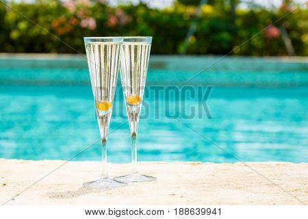 Two Glasses Of Prosecco Cocktail With Orange Berry At The Edge Of A Resort Pool. Concept Of Luxury V
