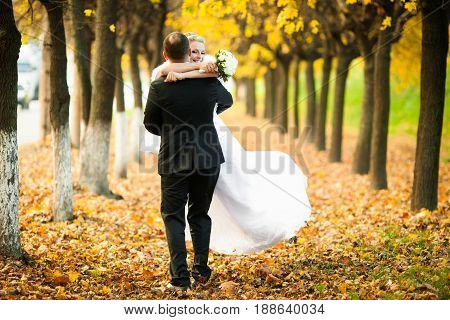 Groom Whirls A Happy Bride On The Path Full Of Fallen Leaves