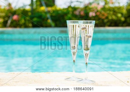 Two Glasses Of Prosecco  Cocktail With Blueberries At The Edge Of A Resort Pool. Concept Of Luxury V