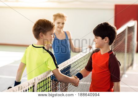Good game. Joyful two boys and shaking hands after playing tennis. They are looking at each other and smiling. Girl is standing on background