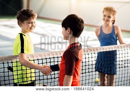 Lets play. Confident two kids are starting competition by handshake. They are standing and separated by tennis net. Girl is looking at them and smiling