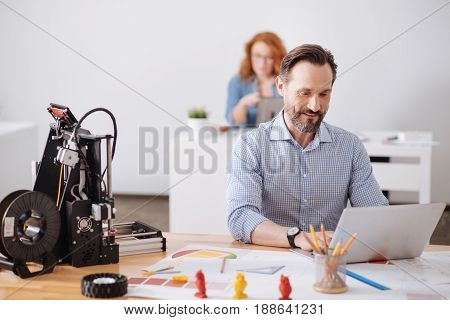 Computer modeling. Cheerful delighted handsome man working on the laptop and developing a new 3d design while sitting at the table