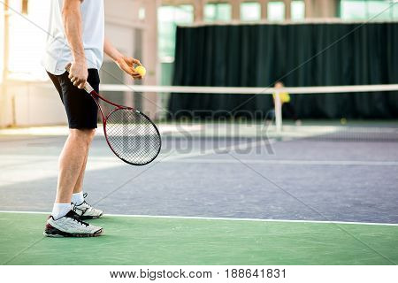 Close up of male legs standing on court while playing tennis. Man is ready to throw a ball by raising the racket. Copy space