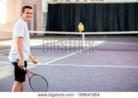 Portrait of happy young man plying tennis with enjoyment. He is looking at camera and smiling. His opponent is standing on background. Copy space