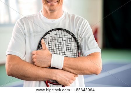 Everything is okay. Joyful young man is giving thumb up while hugging the racket. He is standing and smiling. Close up of his arms