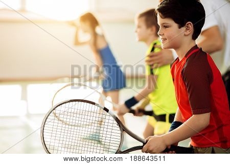 Portrait of happy boy is waiting for ball while holding tennis racket. He is looking forward with anticipation and smiling. Other kids and trainer on background