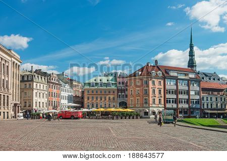Square With People And Spire Of Ssint Peter Church Riga