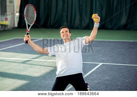 I won. Excited young man is celebrating his triumph in tennis game. He is kneeling on tennis court and laughing. Athlete is holding racket and ball