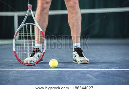 Close up of sportsman feet standing on court near tennis ball on floor. Focus on racket and ball
