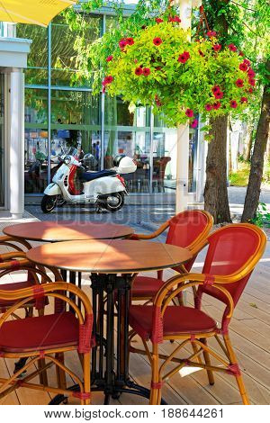 Jurmala Latvia - August 18 2013: Street cafe with tables and chairs and scooter parked at the building Jurmala Latvia recreational resort