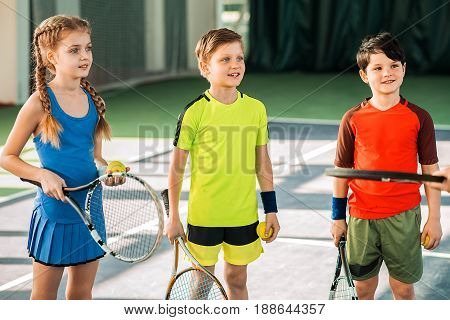 Excited children are listening to trainer with interest. They are standing on tennis court and smiling. Man is showing tennis racket to them. Portrait