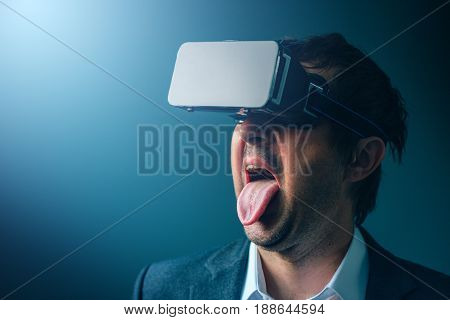 Satisfied businessman with his tongue out wearing VR goggles headset enjoying virtual reality multimedia content or watching a 3d business presentation