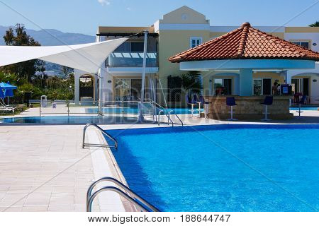 Hotel outdoor swimming pool with clear water and bar.