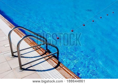 Ladder of pool and rope with buoys of hotel outdoor swimming pool.