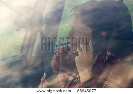 Smiling woman talking on mobile phone in car satisfied adult female person during telephone conversation