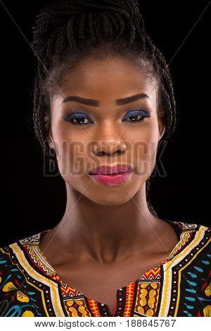 Dark skinned model posing on black background. Beautiful model with blue eyeshadow and pink lips posing in studio. Close up portrait of dark skinned model.
