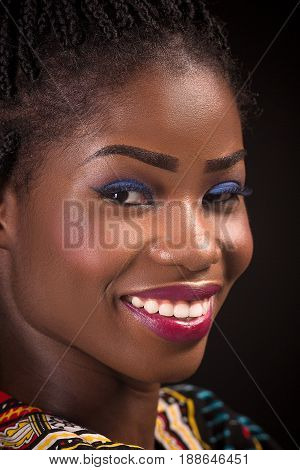 Dark skinned model with open smile on a black background. Close up portrait of smiling woman showing white teeth. Dark skinned model with blue eyeshadow and pink lipstick.