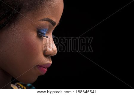 Dark skinned model posing on black background. Close up portrait of dark skinned female with bright make up. Side view portrait of beautiful model.