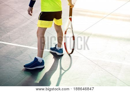 Close up of legs of boy standing on tennis court. He is holding racket. Copy space