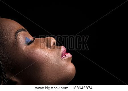 Side view portrait of dark skinned model on a black background. Close up portrait of dark skinned female with bright make up and closed eyes. Side view portrait of beautiful model.
