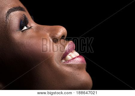 Side view portrait of dark skinned model on a black background. Close up portrait of dark skinned female with open smile showing white teeth. Side view portrait of beautiful model.