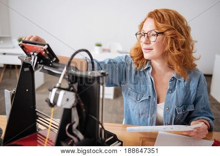 Time to start working. Serious hard working nice woman holding a drawing and pressing a button on the 3d printer while doing a 3d object model