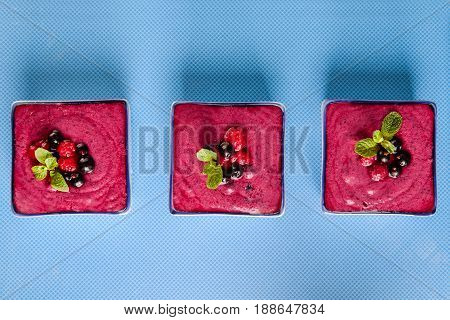 Top View Several Portions Of Berry Smoothie On Blue Ceramic Background. Well Being, Healthy Eating,