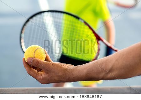 Close up of male hands holding tennis ball in front of racket before pitch