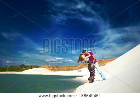 Beach lovers on romantic travel honeymoon vacation summer holidays romance. Young happy lovers, caucasian woman and man embracing outdoors