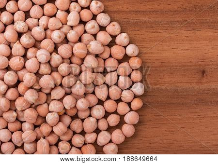 Heap of chick peas chickpeas on a dark board with an empty space for your text. Top view close-up.