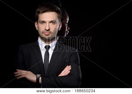 Multi ethnic couple posing on black background. Man in business suit with dark skinned woman behind. Close up portrait of man and woman behind.